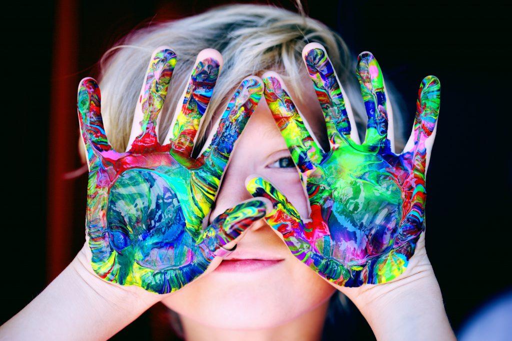 jongen loert tussen zijn geverfde handen