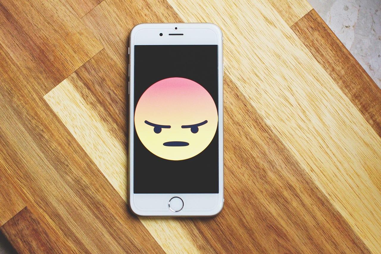 telefoon op een tafel met een boze emoji