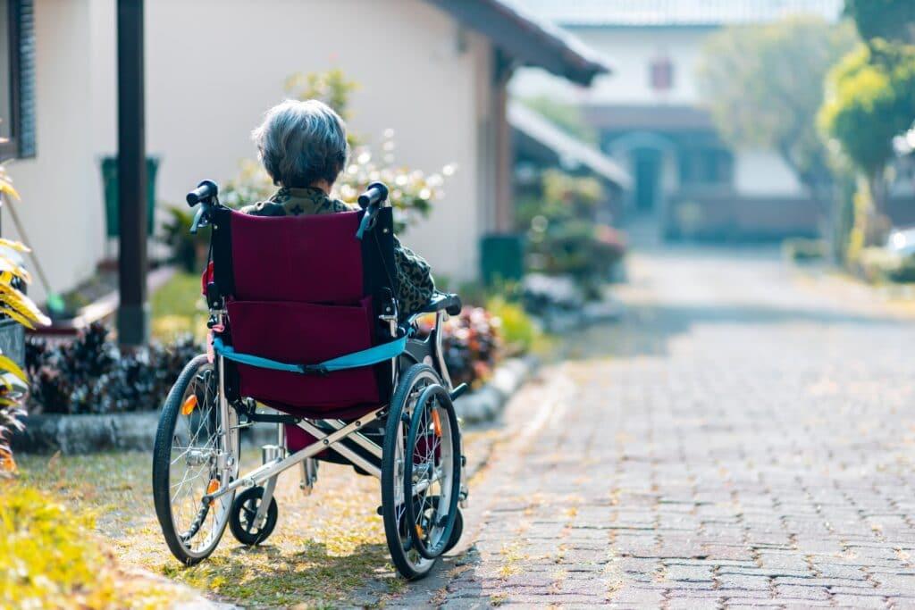 Afbeelding: Vrouw in rolstoel van achteren gefotografeerd