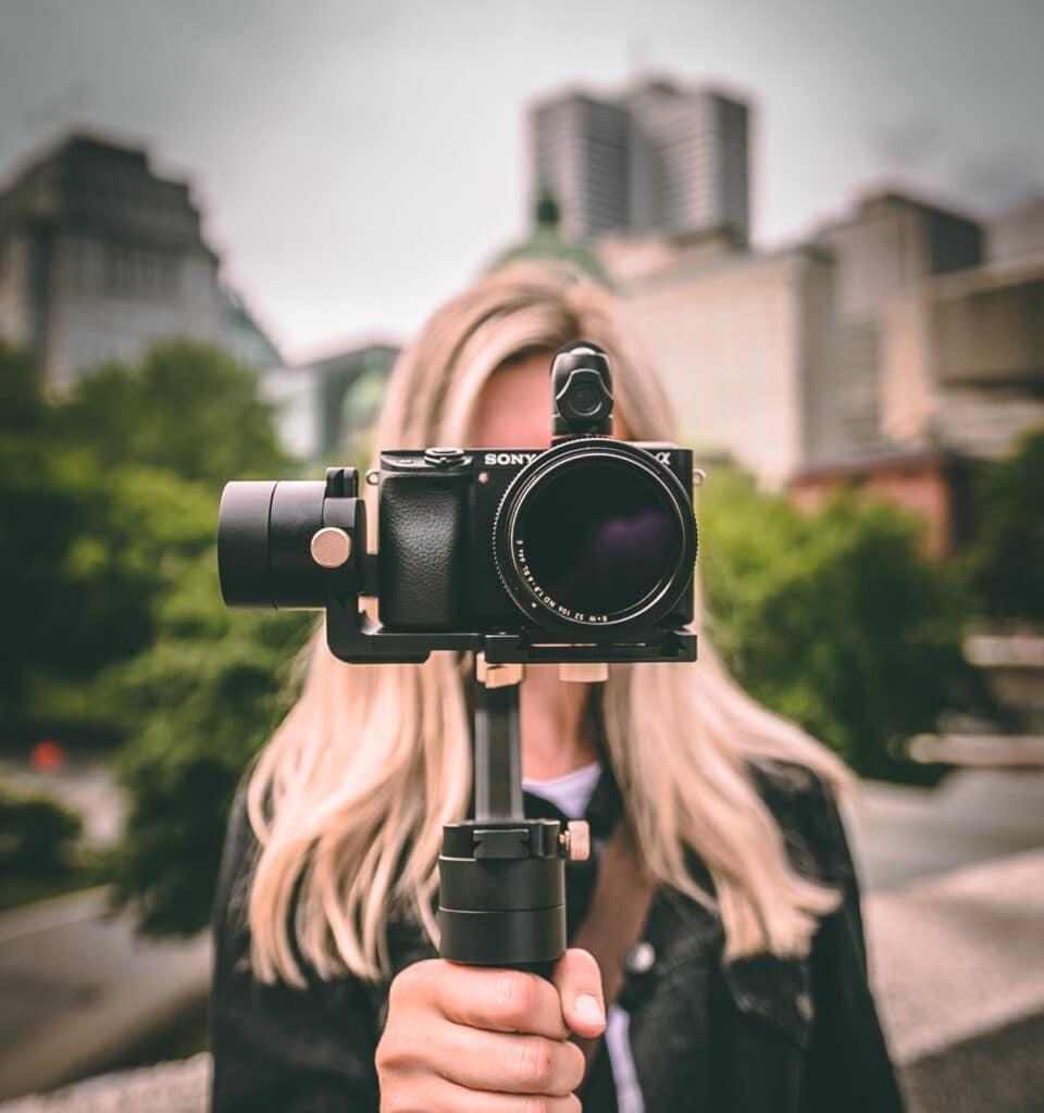 blonde vrouw met camera voor haar gezicht in een stad