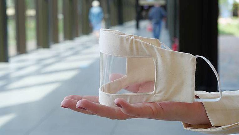 hand met daarop een mondkapje met een transparant venster