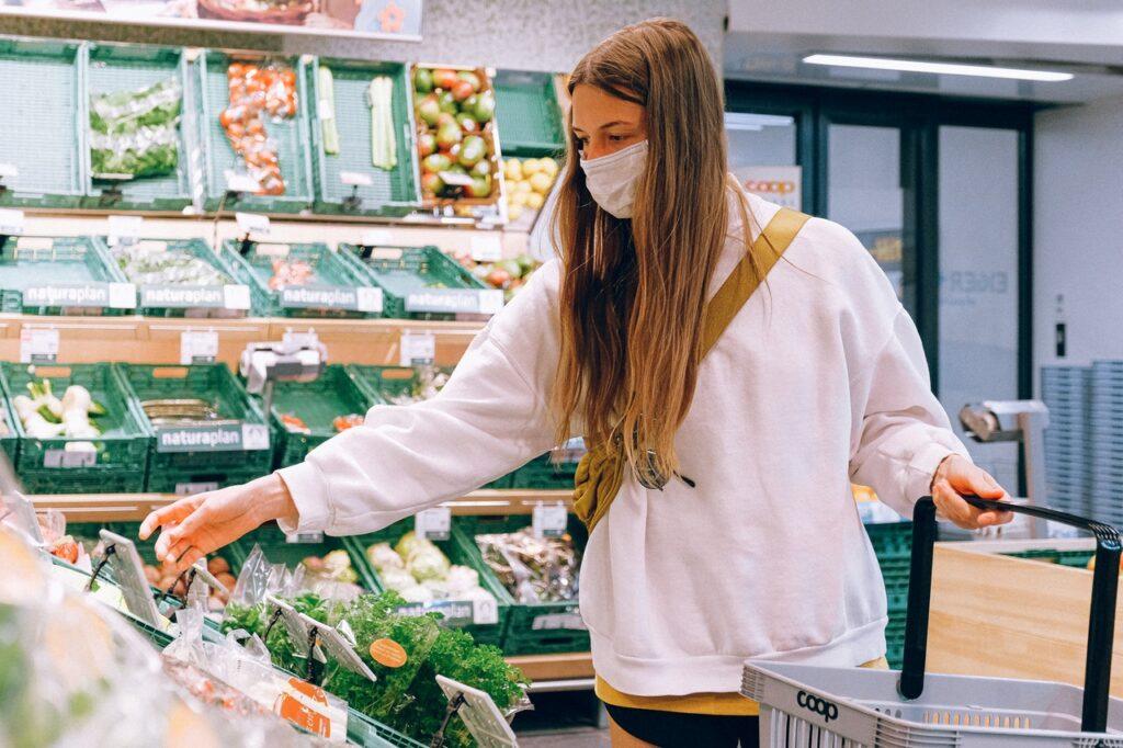Meisje in supermarkt met een mondkapje op