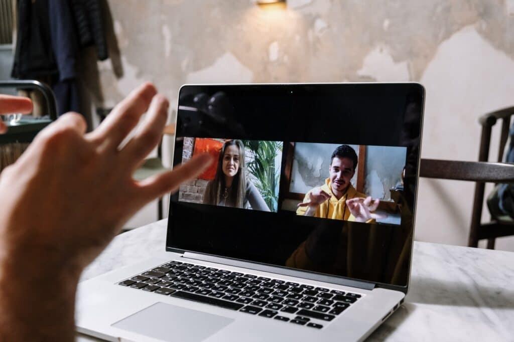 Iemand achter de laptop praat in gebarentaal met twee mensen via een videotool