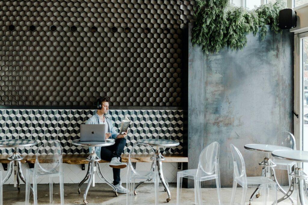 man zit alleen in een leeg café met een hoofdtelefoon op, een laptop open en leest en boek
