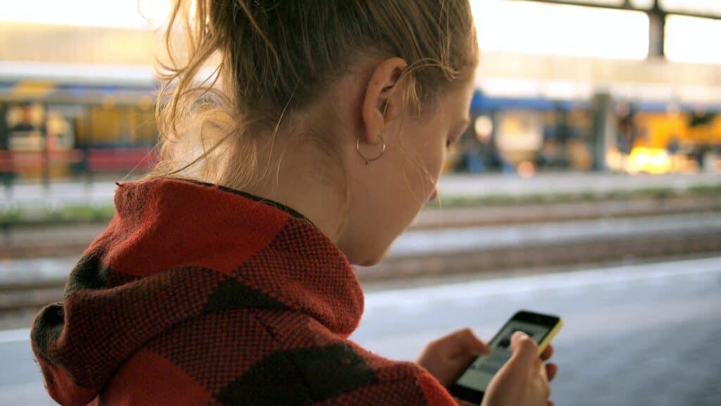 jonge vrouw van achter gezien met mobiele telefoon