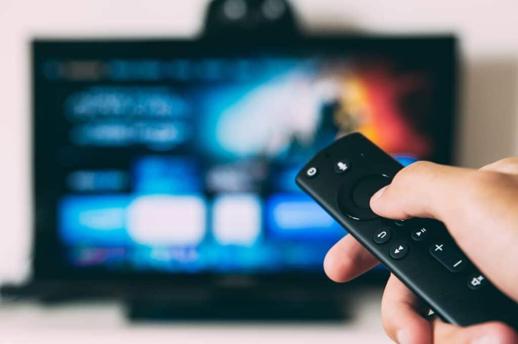 Hand met afstandsbediening en op de achtergrond een onscherpe televisie