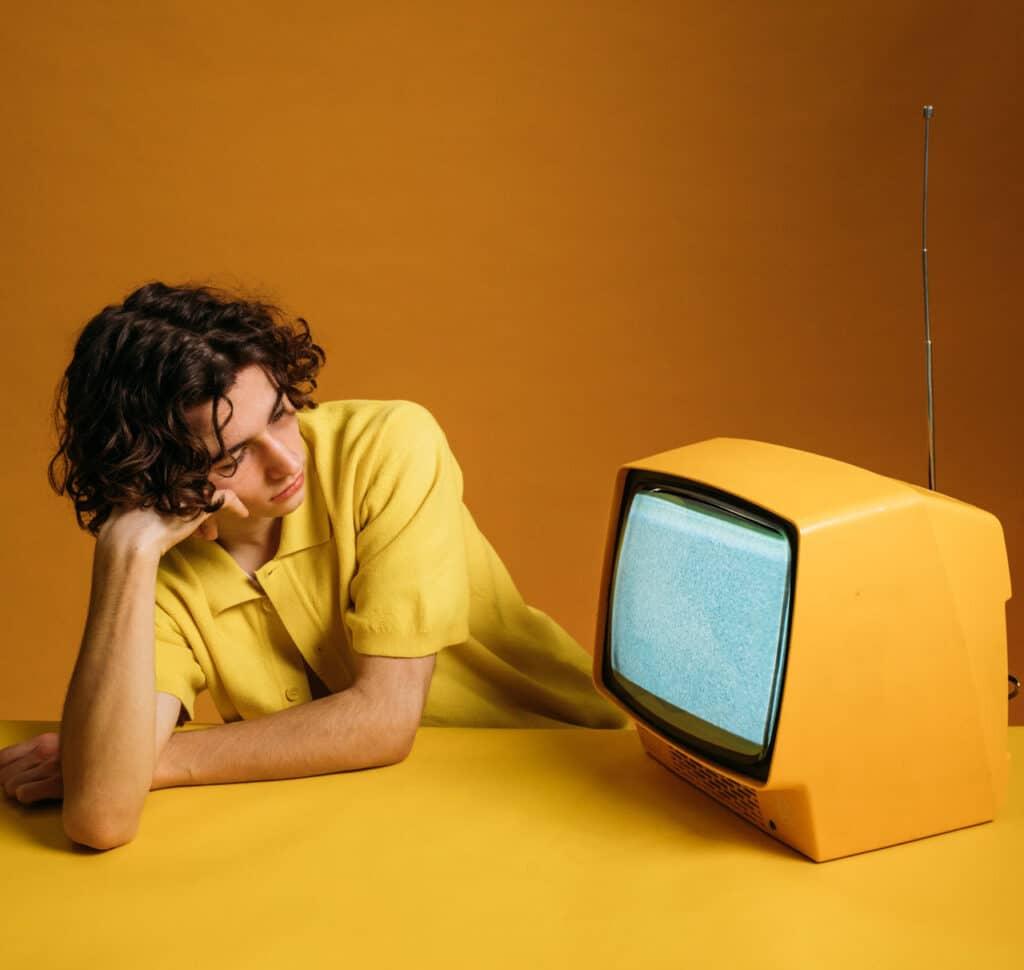 jongen in geel shirt kijkt naar oude televisie