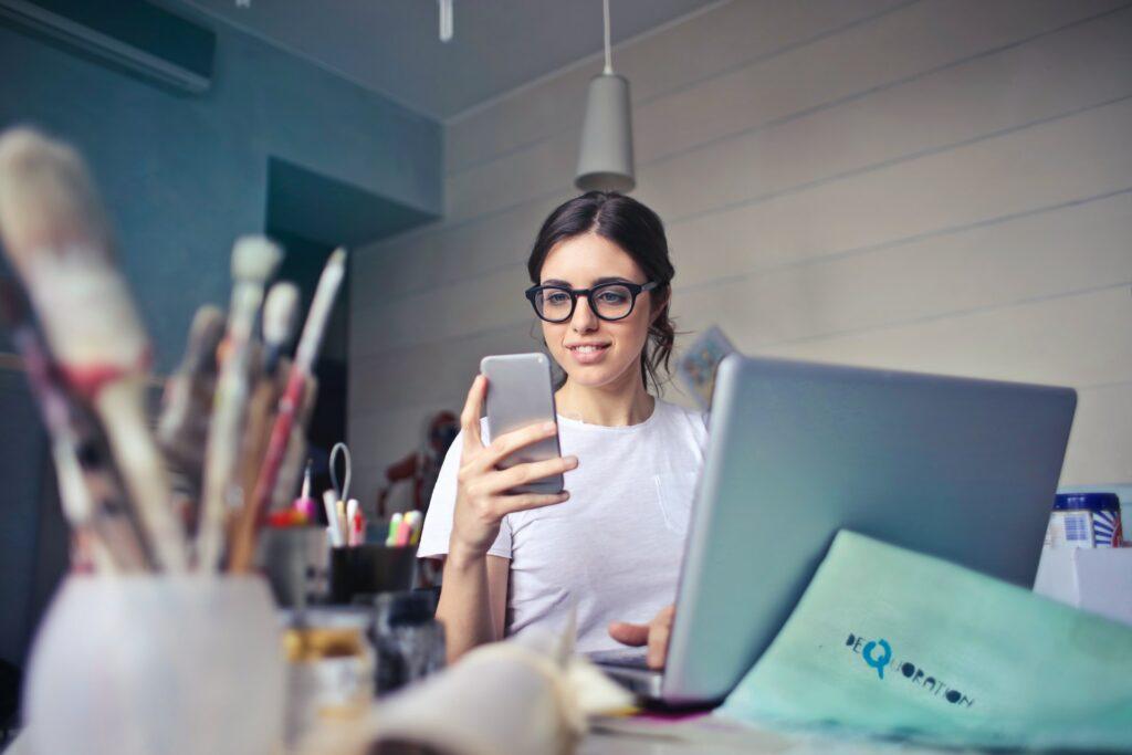 meisje met een telefoon in de hand zit bij een laptop en lacht