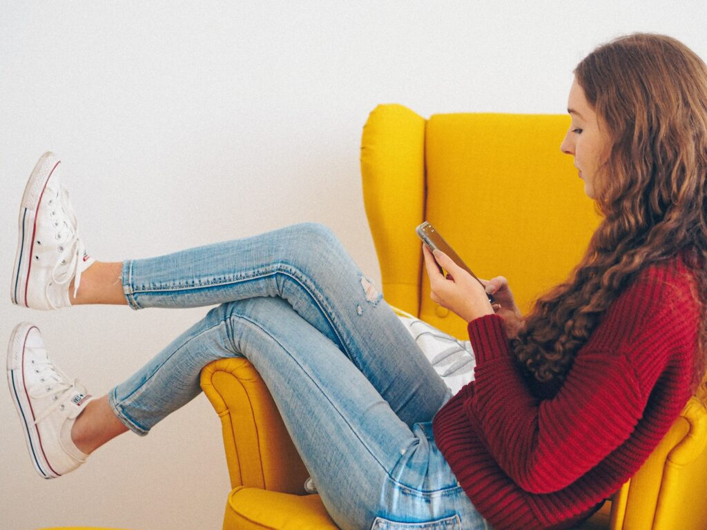 meisje zit op een gele stoel met een telefoon in de hand