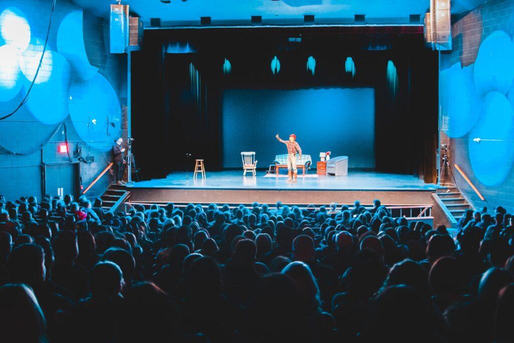 een volle theaterzaal met een acteur op het podium