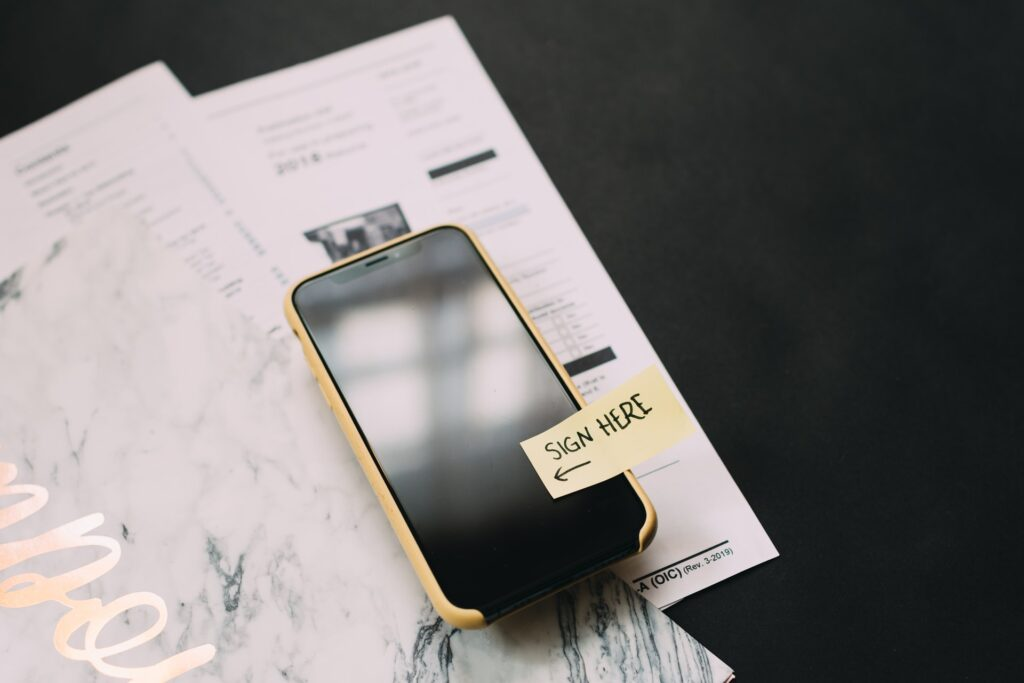 telefoon ligt op een stapel formulieren. Op de telefoon is een briefje geplakt met de tekst 'Sign here'
