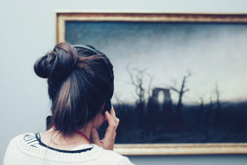 vrouw kijkt naar schilderij met koptelefoon op