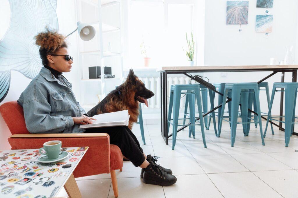blinde vrouw zit op rode bank met hond naast zich
