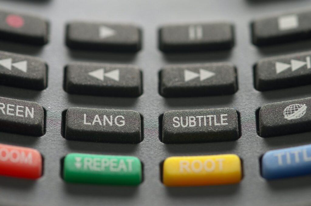 Close-up van een afstandsbediening waarop de knop 'Subtitle' groot in beeld is.