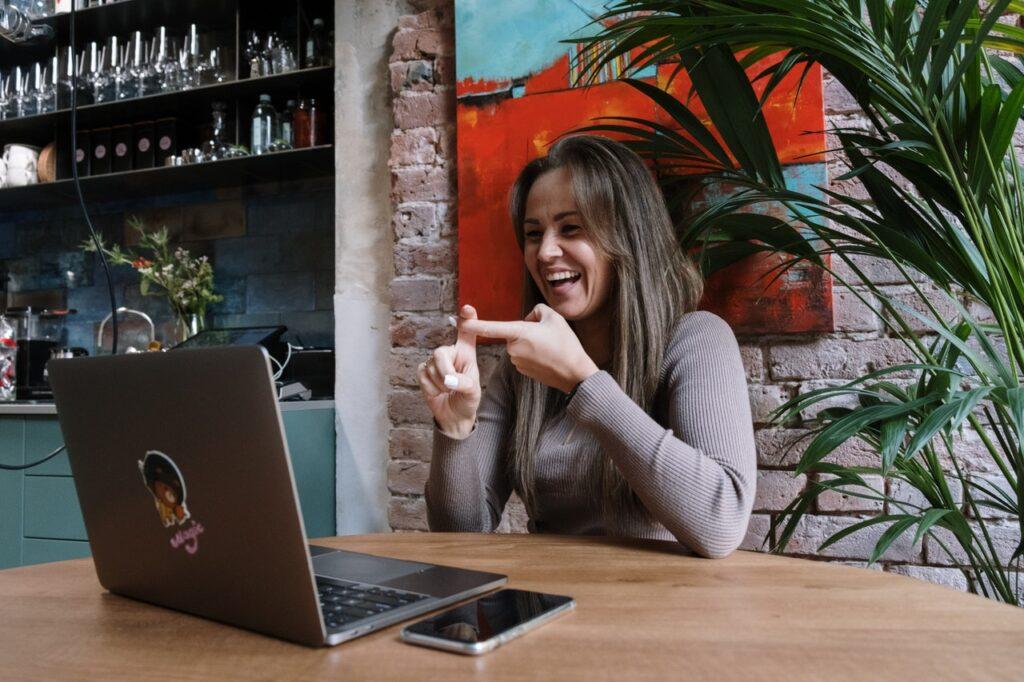 vrouw zit aan tafel met laptop en communiceert in gebarentaal