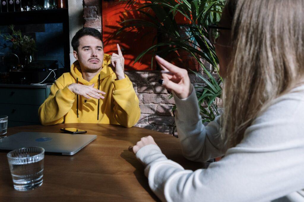 man en vrouw in cafe communiceren met elkaar in gebarentaal