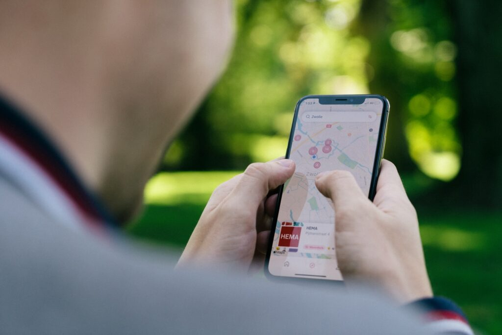 man in de rug gezien gebruikt een app op zijn mobiele telefoon