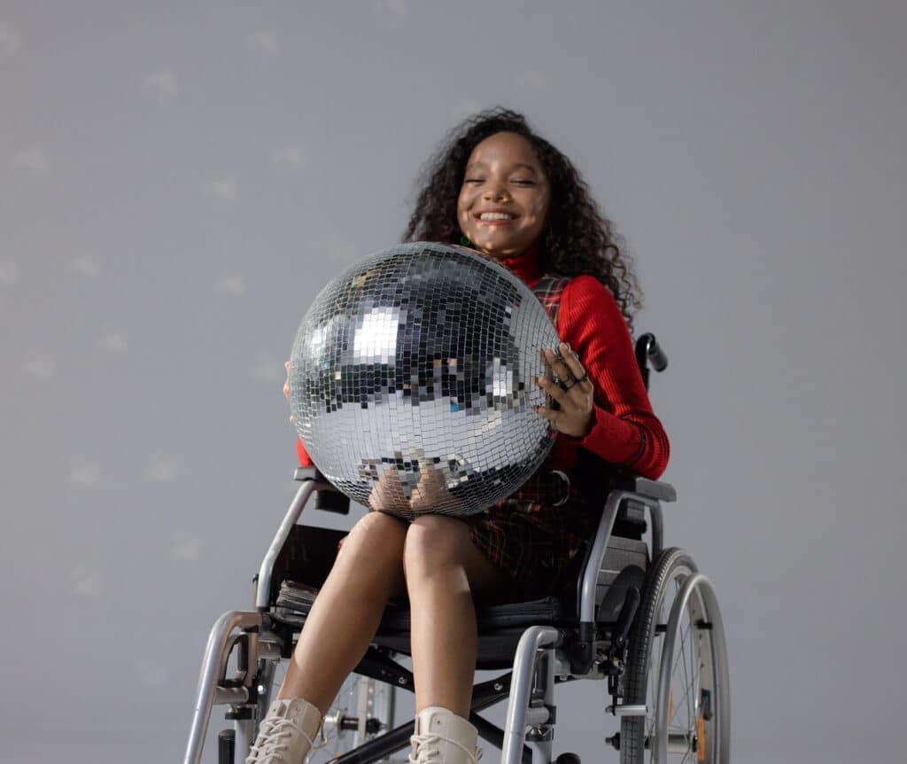 Lachend meisje in rolstoel met discobal