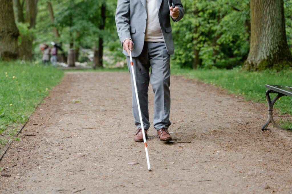 blinde man loopt met stok door park