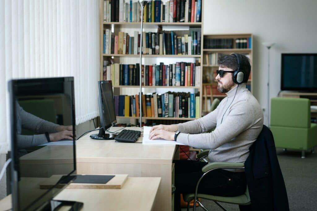 Blinde man met koptelefoon zit achter computer
