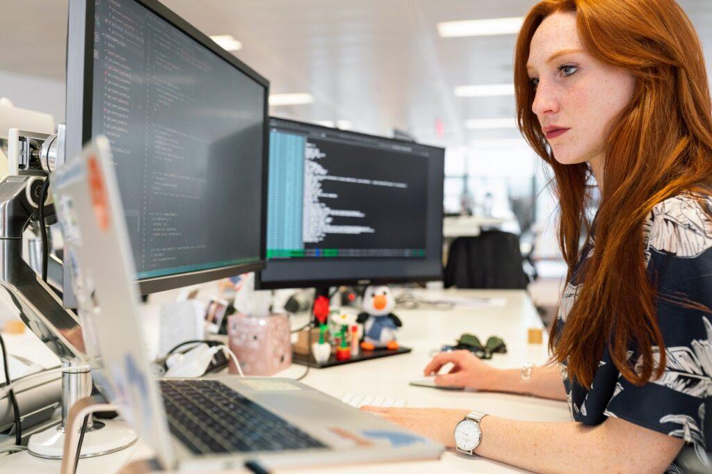 vrouw met rood haar zit achter computer te programmeren